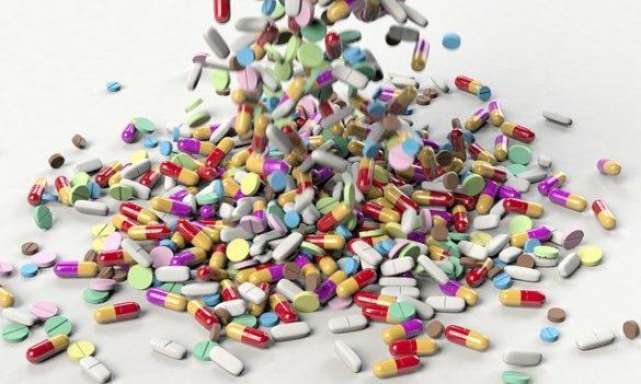 Diversas cápsulas, comprimidos e medicamentos genéricos que são vendidos em farmácia caindo em uma mesa