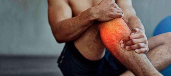 Homem agarrando uma de suas pernas por conta de câimbras musculares