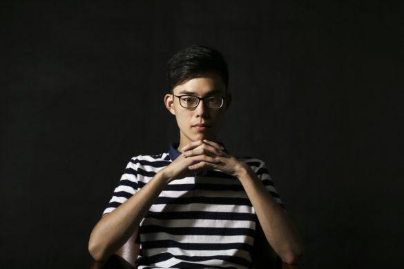Jovem asiático com sociopatia com olhar sério e os dedos das mãos entrelaçados